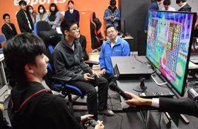 オープンキャンパスでパズルゲーム「ぷよぷよ」の対戦を披露する「飛車ちゅう」さん(左手前)と高校生ら