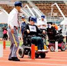 陸上のスラロームで、電動車いすを巧みに操り、赤と白の旗門をすり抜けていく選手=27日、県総合運動公園ニンジニアスタジアム