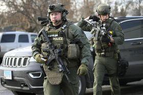 15日、米イリノイ州オーロラで、発砲事件現場に駆け付けたライフル銃を持った警察官(シカゴ・トリビューン提供、AP=共同)