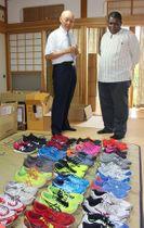 タンザニアの陸上選手のために寄付されたシューズを確認するジョン・F・カンボナ公使(右)と今井雄一さん=22日、南魚沼市下原新田