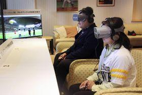 ソフトバンクの5G通信システムを使い、VR端末を装着してプロ野球オープン戦の立体的な中継映像を楽しむ観客=21日午後、福岡市のヤフオクドーム