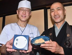 わらび餅「瑞雪」を手にする海野義範布教師(右)と高橋忍店主