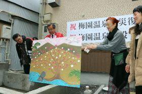 足湯に設置する壁画を披露する梅園温泉組合の平野芳弘組合長(左から2人目)ら=12日、別府市元町の梅園温泉