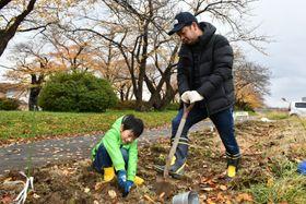 美しい花が咲くように思いを込めて球根を植え替える親子