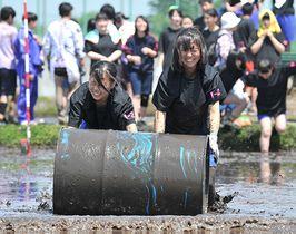 泥だらけになりながらドラム缶を転がす生徒=新庄市・新庄神室産業高