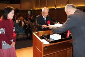 岸川佐世保支社長(右)から表彰状を受け取る吉岡さん夫妻=アルカスSASEBO