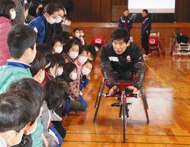 競技用の車いすに乗ってみせる永尾さん=敦賀市中央小で