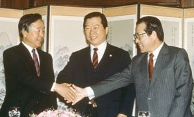 金泳三氏(左)、金大中氏(中央)と握手を交わす金鍾泌氏=1989年、ソウル(聯合=共同)