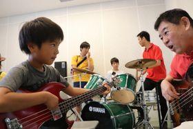 指導を受けながらベースを弾いてみる参加者(左)=とぎつカナリーホール