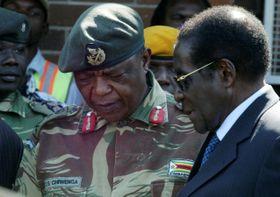 ジンバブエのチウェンガ国軍司令官に話しかけるムガベ大統領(右)=2008年7月、ハラレ(ロイター=共同)
