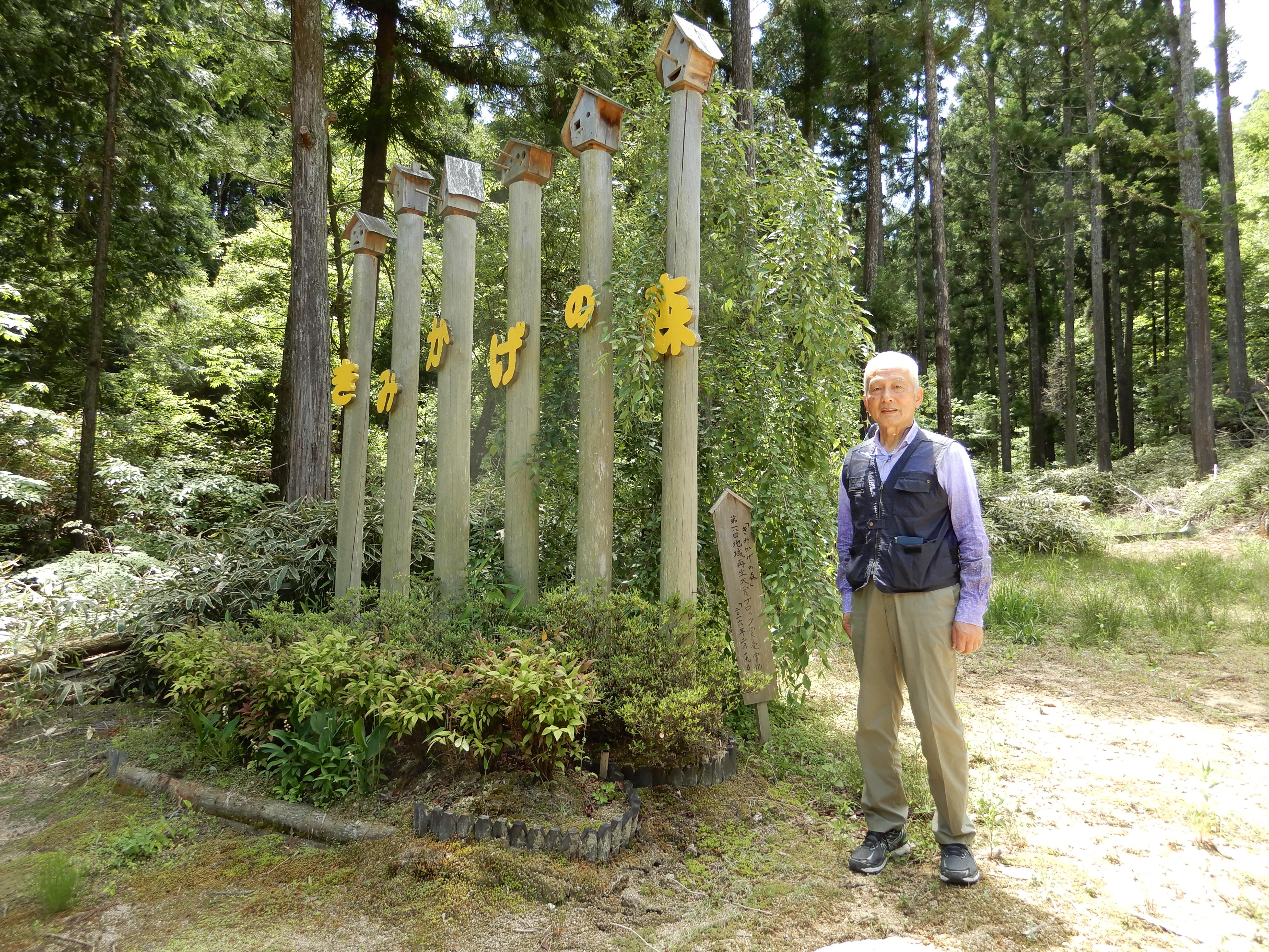 ステージを設け、集いの場を目指して取り組む森の入り口に立つ森岡正宏理事長=2018年5月、奈良市