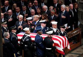 5日、国葬が行われるワシントン大聖堂に入り、長男のブッシュ元米大統領(左下)の横を通り過ぎるひつぎ(ロイター=共同)