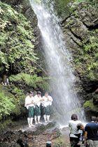 山伏姿の3人が滝に打たれる「滝入りの儀」。観光客の安全を祈った=8日午前11時40分ごろ、越生町の黒山三滝