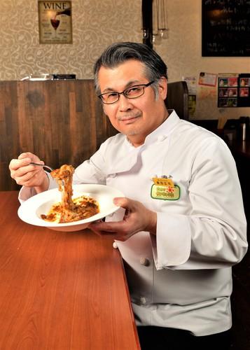 杵つき餅カレーの皿を持つ奥田広司シェフ