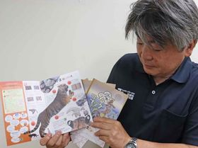 正解を探して書き込む「みんながつくるワークブック」を手に持つ坂本副園長(京都市左京区・市動物園)