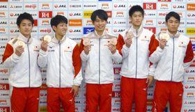 体操の世界選手権から帰国し、記者会見でメダルを手にする(左から)神本、谷川翔、萱、橋本、谷川航=15日、成田空港