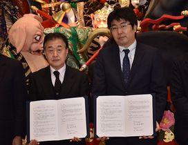 署名した協定書を手にする塚原委員長(左)と塚本執行役員