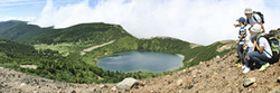一切経山山頂付近から眼下に広がる「魔女の瞳」とも称される五色沼などの大パノラマを堪能する登山者=10日午後、福島市