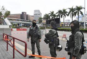 香港理工大(左奥)周辺で通行を規制する警官隊=20日、香港(共同)