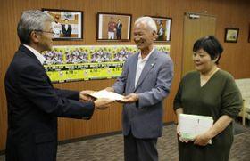 藤原理事長(中央)にチケットを手渡す松尾理事長