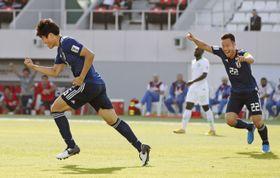 日本―サウジアラビア 前半、先制ゴールを決めガッツポーズで駆けだす冨安。右は吉田=シャルジャ(共同)