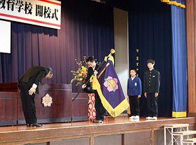米谷教育長(左)から校旗を受け取った寺田校長(左から2人目)=国吉義務教育学校