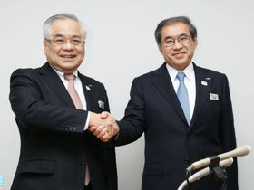 記者会見後に握手する冨田哲郎社長(左)と深沢祐二副社長=20日午後、東京都渋谷区