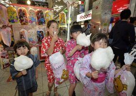 土曜夜市で綿菓子を頰張る子どもたち=23日夕、松山市大街道1丁目