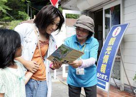 案内所前で観光客にパンフレットを渡す橋本悦子さん(右)=1日、天草市河浦町