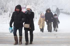 16日、ロシア・サハ共和国で、極寒の中を歩く人々(タス=共同)