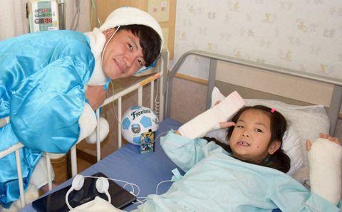 入院中の子どもたちにクリスマスプレゼントを贈った長谷川選手(左) =関東労災病院