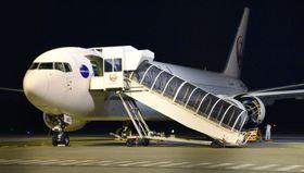 エンジントラブルを起こし、機体から部品が落下した日航機=24日午後8時14分、熊本空港