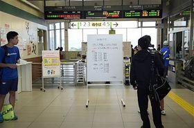 JR八戸駅の改札前で、列車運休の情報を確認する利用客=20日午前8時5分ごろ