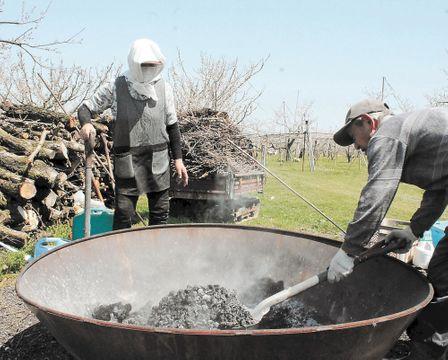 剪定枝を焼却して生じた炭を専用の器具から掘り出す高橋さん夫妻