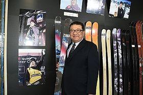シャープ選手が使用した自社ブランド「ZUMA」のスキー板を手にする社長の丸山さん。左の写真はシャープ選手=飯山市のスワロースキー本社