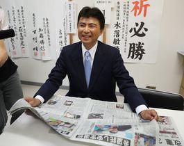 選挙結果を伝える新聞を手に笑顔を見せる古賀友一郎さん=長崎市の事務所