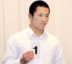 抽選会で番号札を読み上げる済美・山田主将=21日、徳島市
