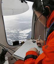 航空機から流氷観測する第1管区海上保安本部の観測員=17日午前、北海道紋別市沖のオホーツク海