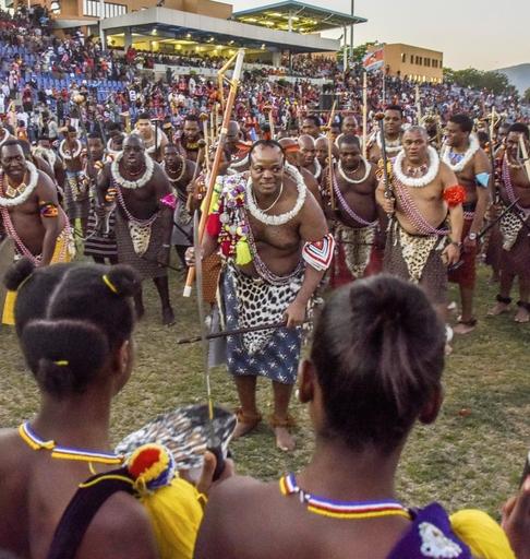 伝統行事ウムフランガで踊りを披露した女性たち(手前)に感謝を示す国王ムスワティ3世(中央)。背後に多数の王族を従えている=19年9月、ムババーネ郊外(共同)
