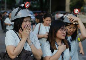フィリピンでの地震発生後、ヘルメットをかぶり避難する人々=22日、マニラ(AP=共同)