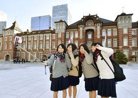 改修工事が完了したJR東京駅丸の内側の広場で、記念撮影する修学旅行の高校生=7日午前、東京都千代田区