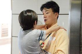 廊下で子どもを抱っこして話を聞く副島賢和さん=東京都品川区の昭和大病院