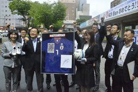 横断幕(右上)を背に柴崎岳選手から寄贈されたサイン入りグッズを囲む三村申吾知事(左から3人目)ら=13日、県庁
