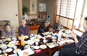 「女子講」で観音様のお掛け絵(後方)を祭り会食を楽しむ女性ら=長崎県平戸市春日町
