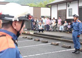 避難した入所者の前で訓練を総括する西消防署の林田隊長(右)=佐世保市吉井町