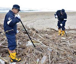 砂浜の漂着物を棒でかき分け、手掛かりを捜す署員ら=11日午前10時10分ごろ、いわき市・夏井川河口