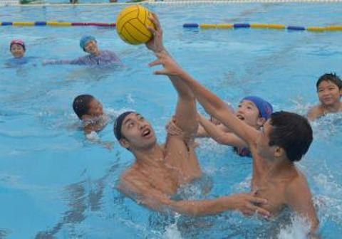 子どもたちとボールを奪い合う大川慶悟選手(中央)=土浦市の土浦二高
