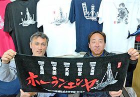 オリジナルグッズのタオルを手にホーランエンヤのPRに意欲を燃やす松尾和夫さん(左)と今川淳一郎さん=松江市馬潟町