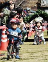 ランニングバイク選手権でコースを駆け抜ける子どもたち