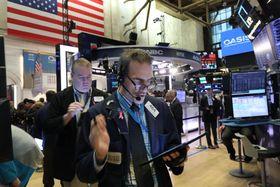 ニューヨーク証券取引所のトレーダーたち=25日(ゲッティ=共同)